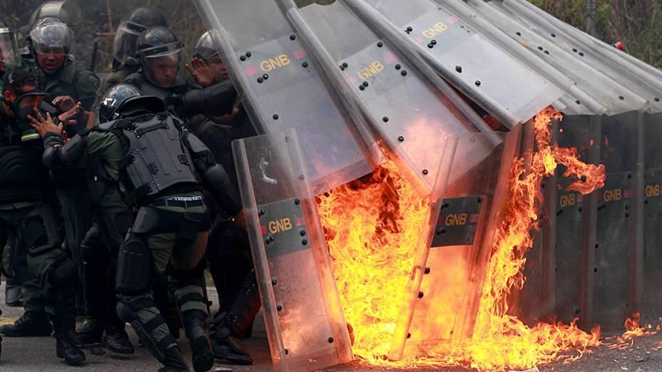 Membros da Guarda Nacional Venezuelana reagem após serem atingidos por um coquetel molotov jogado por estudantes durante confrontos na Universidade Metropolitana de Caracas
