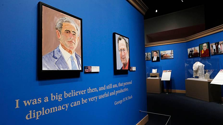 """Auto-retrato do ex-presidente George W. Bush e de seu pai, o também ex-presidente dos EUA George H.W. Bush, saúdam os visitantes na entrada da exposição """"A Arte da Liderança: Diplomacia Pessoal de um Presidente"""" na Biblioteca e Museu Presidencial Bush, em Dallas, no Texas"""