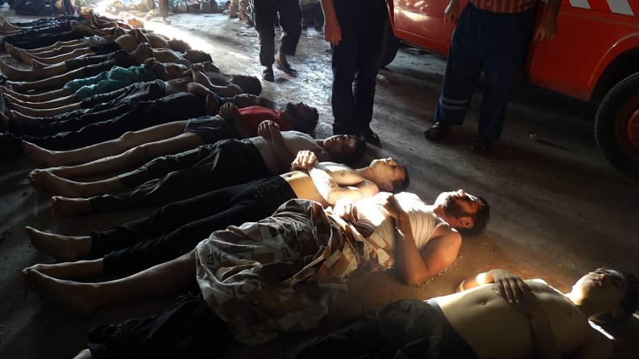 Parentes e ativistas inspecionando os corpos das pessoas que podem ter sofrido um  ataque por gás na região de Ghouta, nos arredores de Damasco