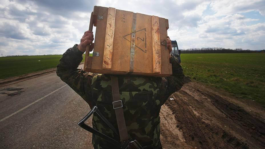 Soldado ucraniano leva uma caixa de munição para as tropas que aguardam nos arredores da cidade de Izium, ao leste do país