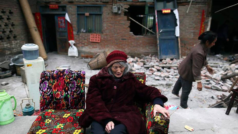 Idosa senta em um sofá na frente de casas destruidas por terremoto na cidade de Taiping Lushan, província de Sichuan, China