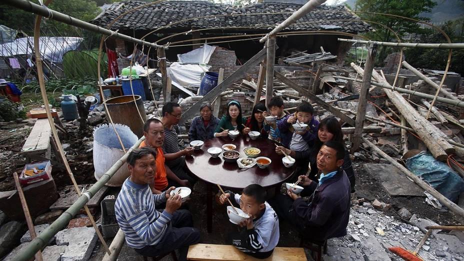 Moradores locais tem uma refeição em família fora de sua casa destruida pelo terremoto que atingiu o condado de Lushan, na província de Sichuan, China