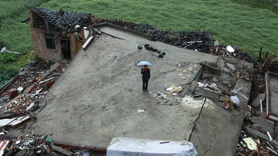 Mulher vê sua casa destruída pelo terremoto que atingiu o condado de Lushan, na província de Sichuan, China
