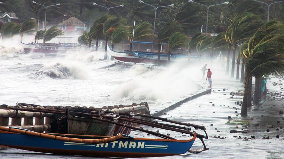Moradores passam por chuva e ventos fortes, após tufão Haiyan atingir a cidade de Legaspi, ao sul de Manila, nas Filipinas
