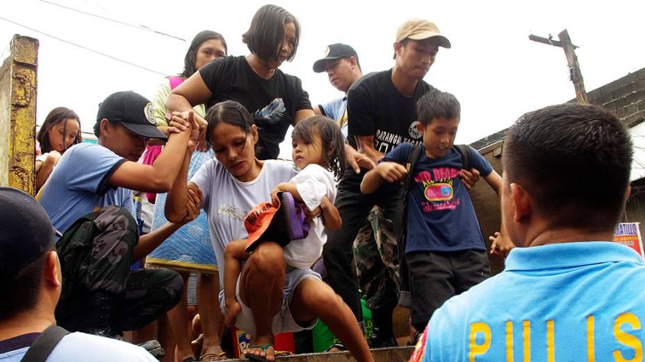 Moradores que vivem perto das encostas do vulcão Mayon são evacuados por causa do tufão Haiyan ter atingido a  província de Albay na região central das Filipinas