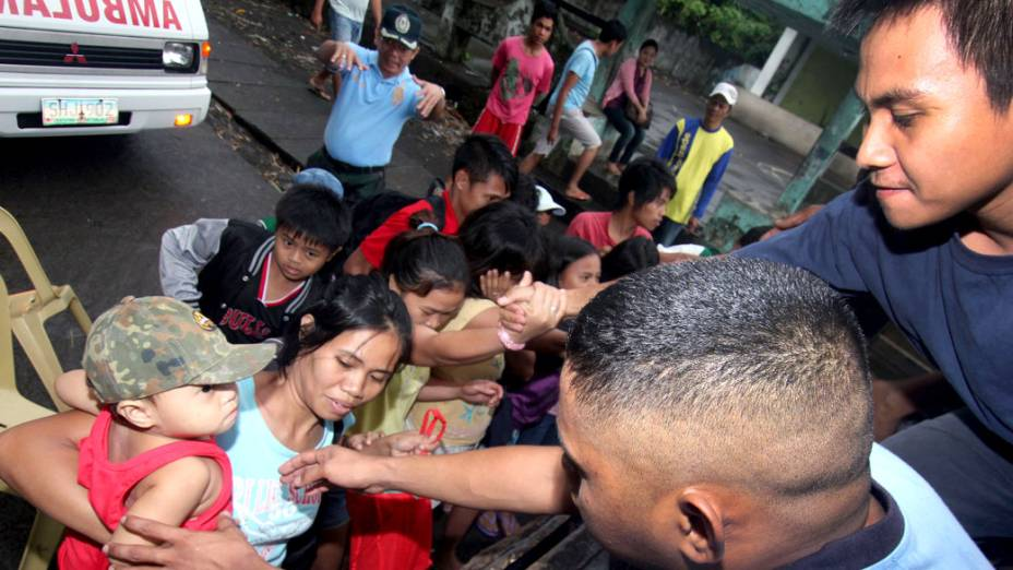 Moradores de uma cidade ao sul de Manila, capital das Filipinas, são evacuados devido à chegada do tufão Haiyan