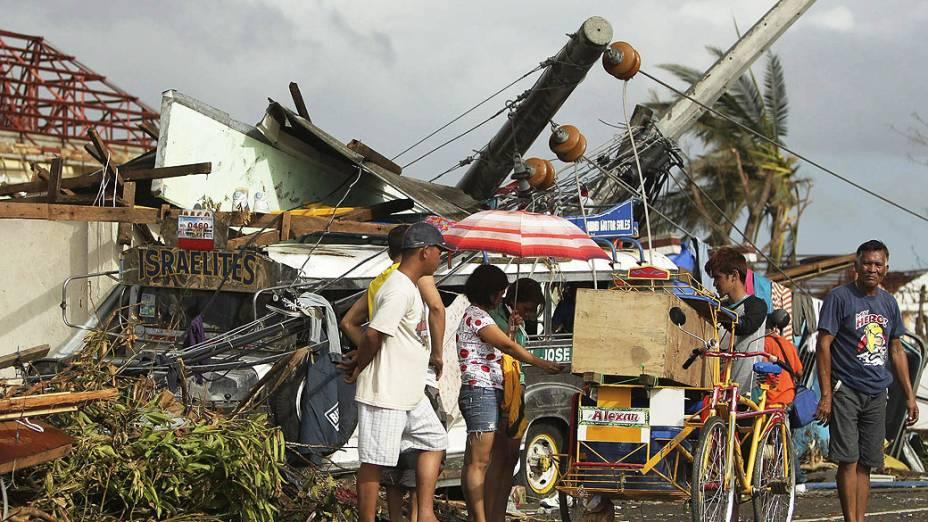 Pessoas passam por destroços causados pelo tufão Haiyan, na cidade de Tacloban, nas Filipinas