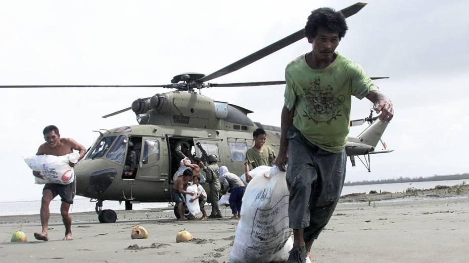 Sobreviventes do tufão Haiyan, da aldeia costeira de Capiz, transportam sacos contendo alimentos entregues pelas Forças Armadas, nas Filipinas