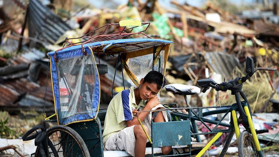 Jovem sobrevivente repousa sobre um triciclo nos destroços causados pelo tufão Haiyan em Tacloban, nas Filipinas