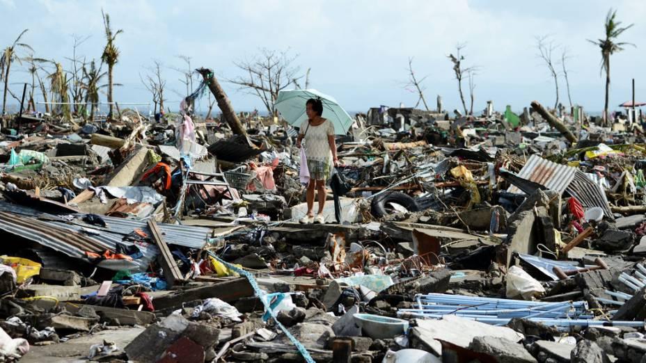 Mulher caminha nos escombros de casas destruídas pelo tufão Haiyan em Tacloban, nas Filipinas