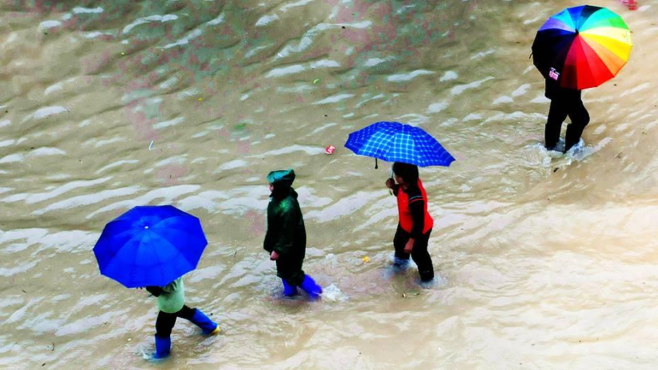 Moradores andam por ruas alagadas na cidade de Tacloban, nas Filipinas