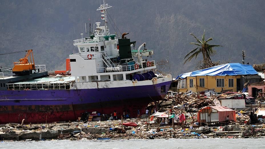 Pessoas caminham entre escombros ao lado de um navio em Anibong, em Tacloban, nas Filipinas