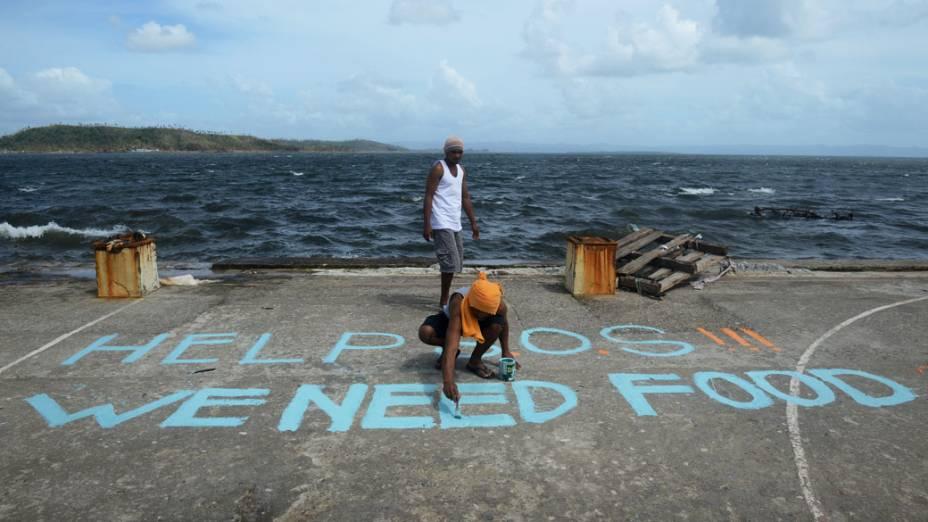 """Homem pinta mensagem """"SOS Ajuda, Precisamos de comida"""" em Tacloban, leste da ilha de Leyte, nas Filipinas"""