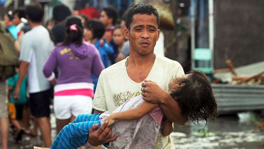 Pai leva o corpo de sua filha para o necrotério depois do tufão Haiyan atingir Tacloban, na província de Leyte, nas Filipinas