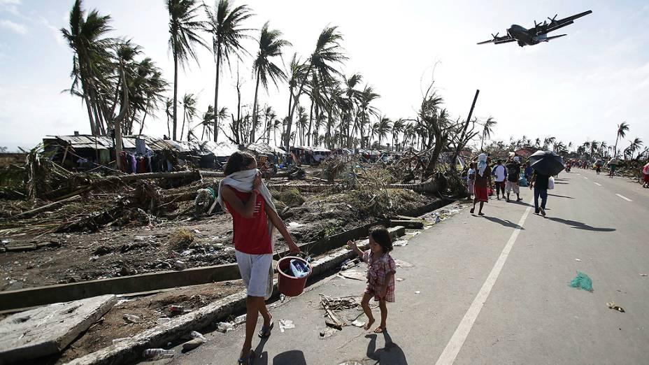 Moradores observam a chegada de um avião C-130 carregado de mantimentos em Tacloban (Filipinas)