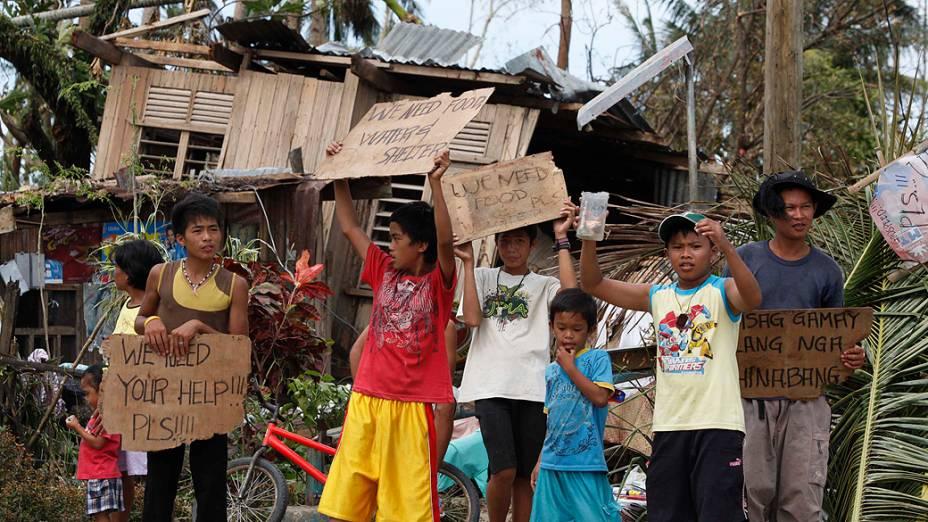 Crianças erguem cartazes pedindo ajuda e comida à beira de uma rodovia em Tabogon, na província de Cebu, atingida pelo tufão