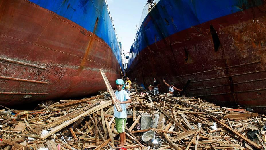 Moradores caminham entre dois navios arrastados pela força das águas em Anibong, no centro das Filipinas