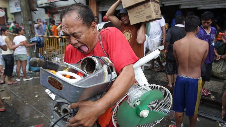 Homem leva suprimentos de loja invadida na cidade de Tacloban, nas Filipinas