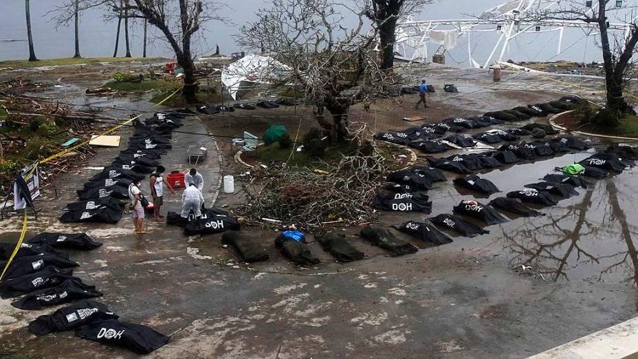 Pessoas observam fila de corpos de vítimas do supertufão Haiyan em Tacloban, nas Filipinas