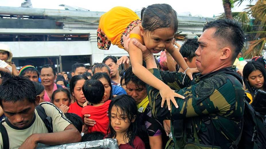 Soldado retira crianças durante a evacuação da cidade de Tacloban