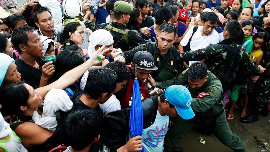 Soldados tentam conter pessoas desesperadas ao tentar embarcar no aeroporto de Tacloban