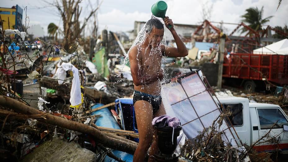 Homem toma banho em meio a escombros na cidade Tacloban, região central das Filipinas