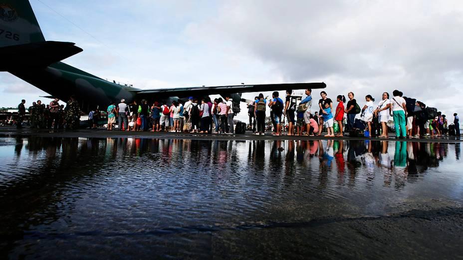 Sobreviventes do tufão Haiyan esperam para embarcar, nesta quarta-feira (13/11), no aeroporto de Tacloban