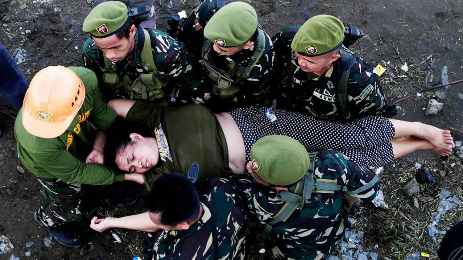 Soldados socorrem mulher que desmaiou ao tentar embarcar em avião em Tacloban, nas Filipinas