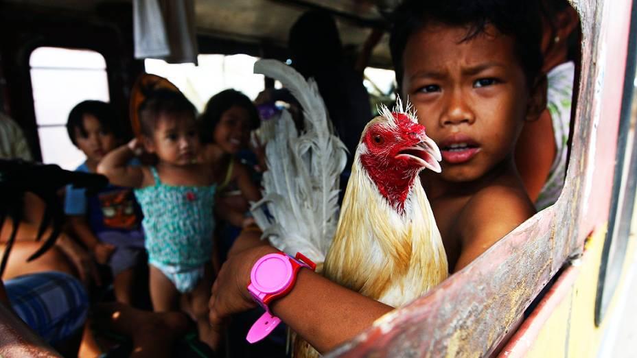 Menino dentro de um ônibus com sua família antes  de deixar a cidade de Tacloban, nas Filipinas