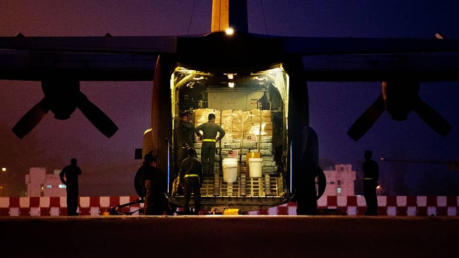 Soldados malásios carregam avião para doar suprimentos às vítimas de tufão