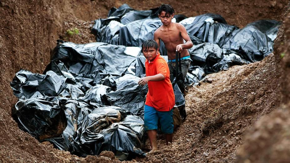Filipinos ajudam a mover os corpos para o enterro em uma vala comum de vítimas do tufão Haiyan na cidade de Tacloban