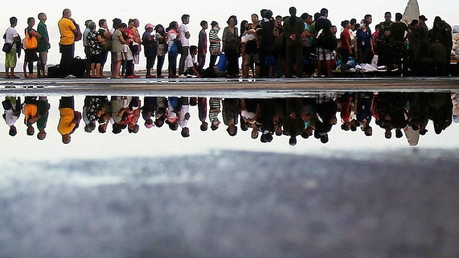 Sobreviventes do supertufão Haiyan aguardam em fila antes de serem transportados por um avião militar no aeroporto de Tacloban
