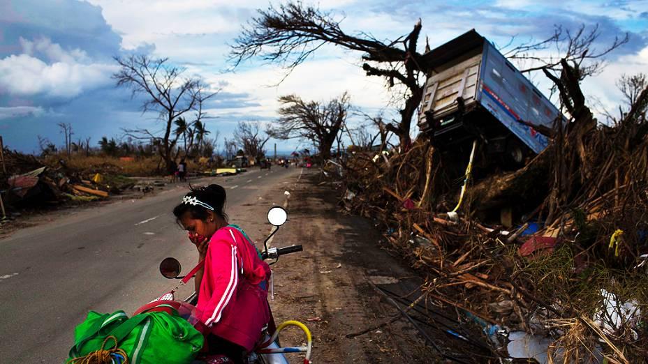 Sobrevivente do tufão Haiyan é fotografada entre ruínas de casas destruídas na cidade de Tacloban