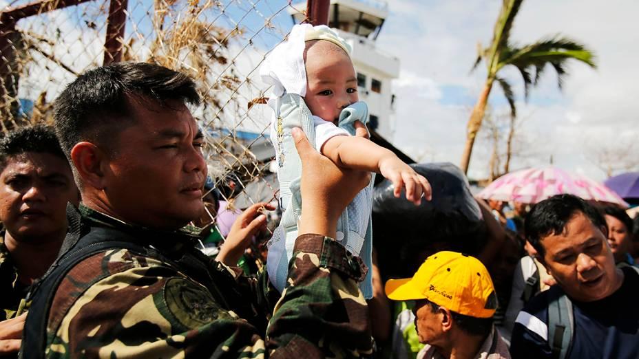 Soldado filipino segura um bebê enquanto passa pelas pessoas no aeroporto de Tacloban