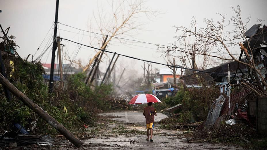 Mulher caminha por rua coberta por destroços causados pelo tufão Haiyan, nesta segunda-feira (18), em Jaro, nas Filipinas