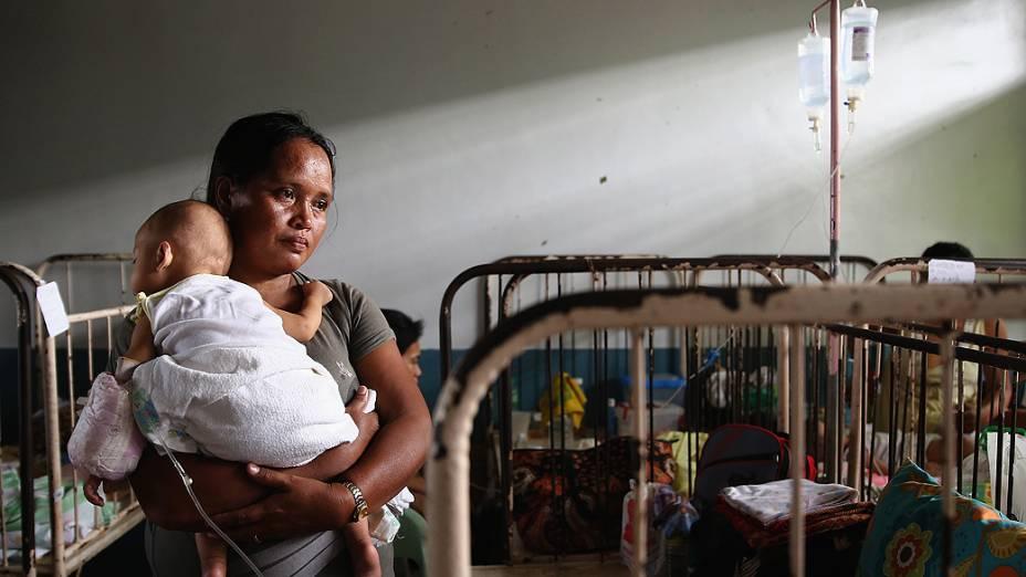 Mulher segura um bebê recém-nascido em uma maternidade em Leyte, nas Filipinas