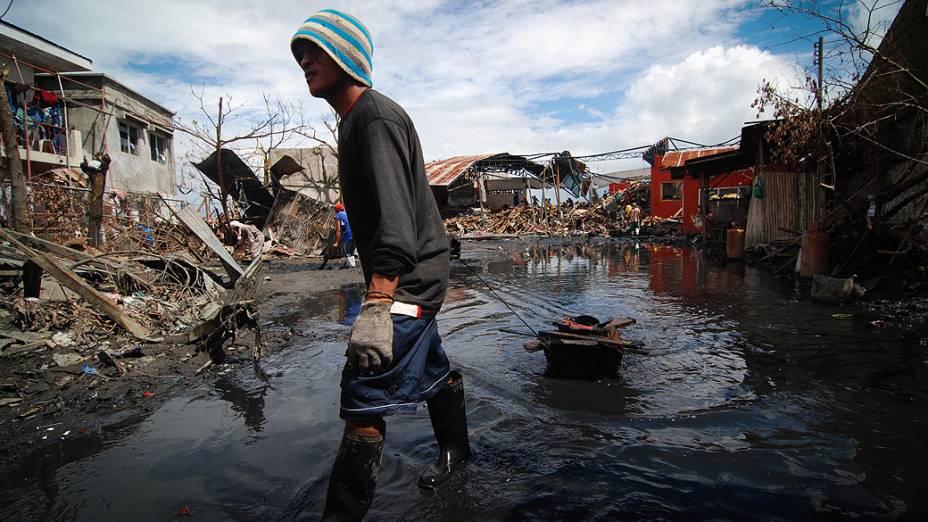 Homem retira lama e detritos em uma área devastada em Tacloban, Leyte, nas Filipinas