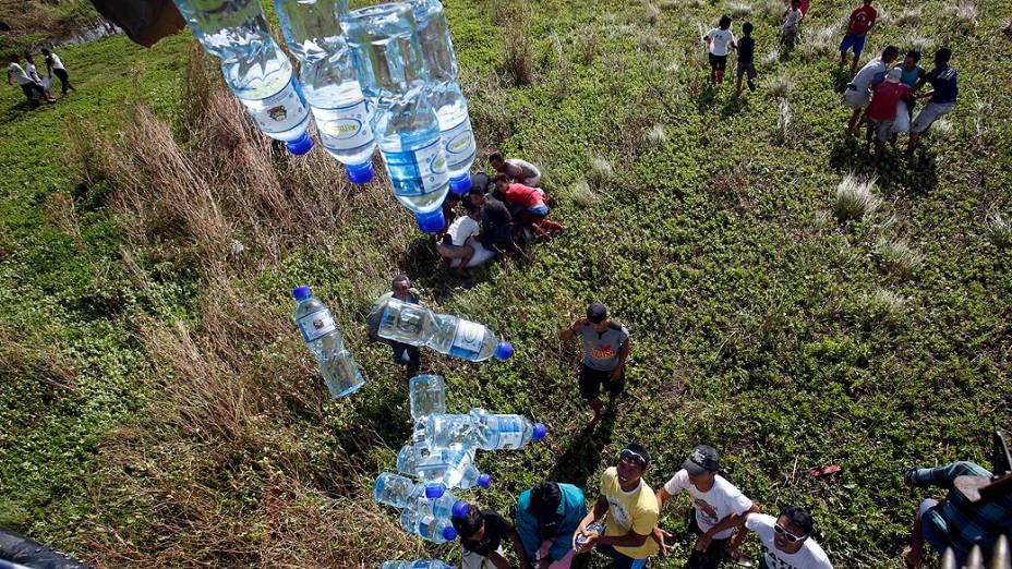 Um helicóptero militar distribui garrafas de água para os sobreviventes do supertufão Haiyan em Tolosa, Leyte, no centro das Filipinas