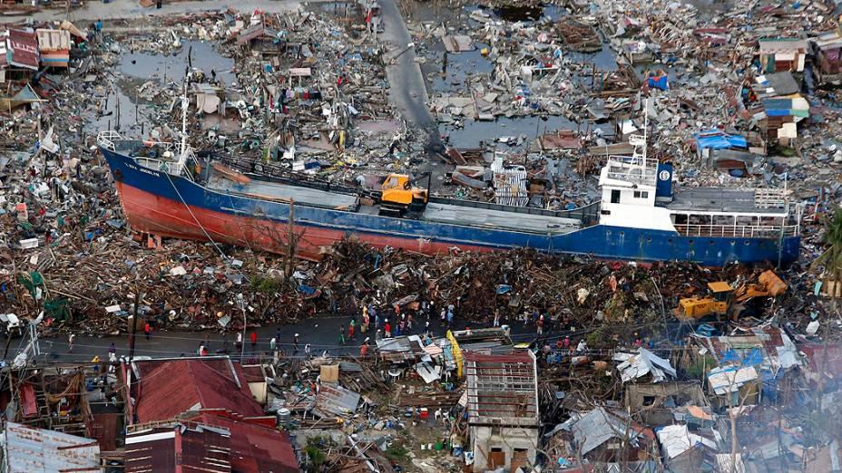 Moradores observam um navio que foi arrastado pelo tufão Haiyan para o centro da cidade de Tacloban, nas Filipinas