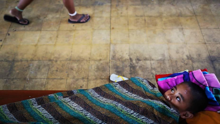 Criança deitada em uma igreja, que se tornou um abrigo improvisado para acolher centenas de sobreviventes do tufão Haiyan em Tacloban