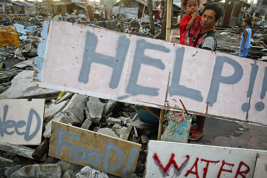 Sobreviventes escrevem mensagens pedindo ajuda para sua comunidade em uma área totalmente devastada pelo tufão Haiyan em Tacloban, nas Filipinas