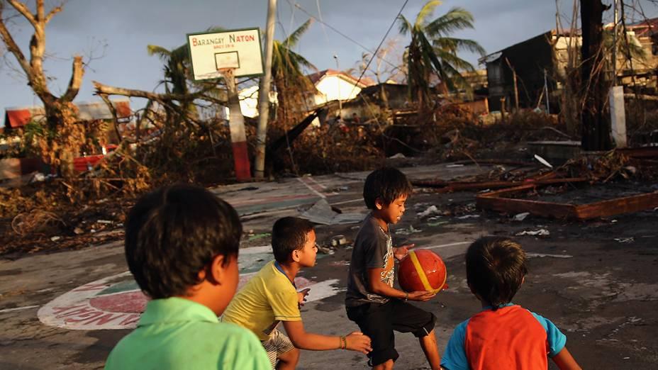 Crianças jogam basquete ao pôr do sol na cidade de Tacloban, nas Filipinas, destruída pela pessagem do supertufão Haiyan