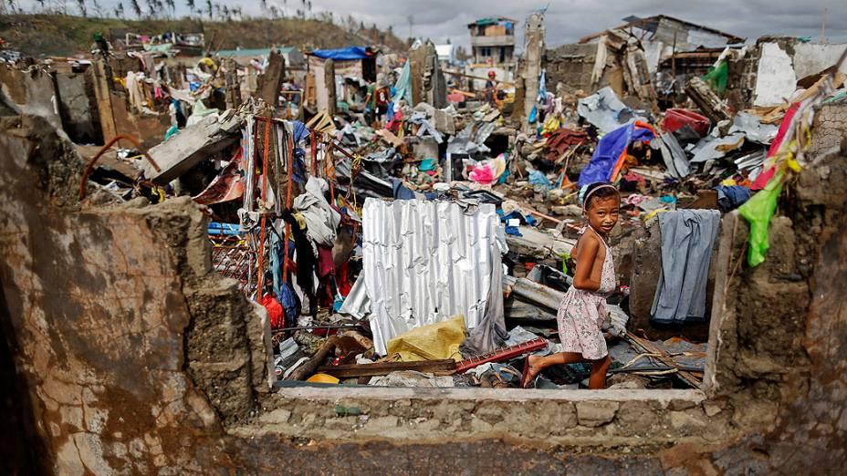 Menina caminha entre as casas destruídas pela passagem do supertufão Haiyan, à procura de pertences e itens que possam ser úteis, na cidade de Tacloban, nas Filipinas