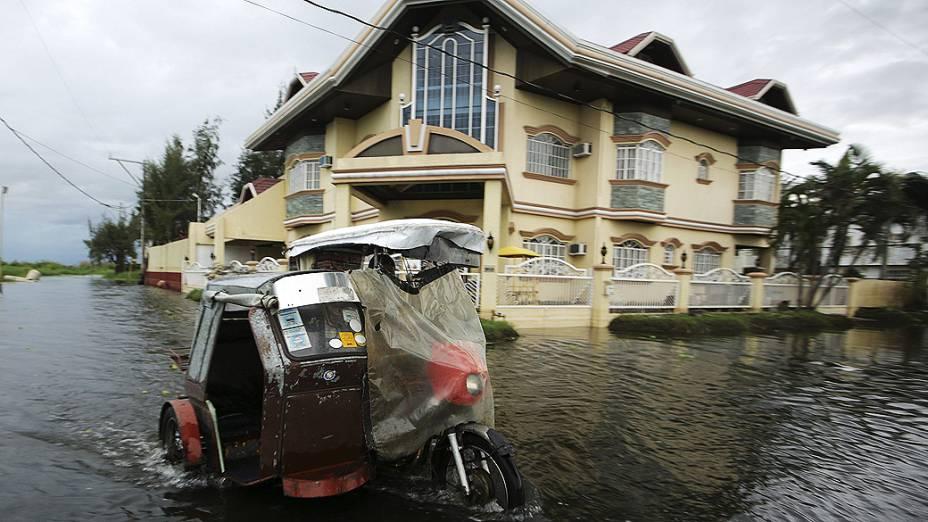 Homem transita com sua moto pelas ruas alagadas de Taguig, nas Filipinas após a passagem do supertufão Haiyan