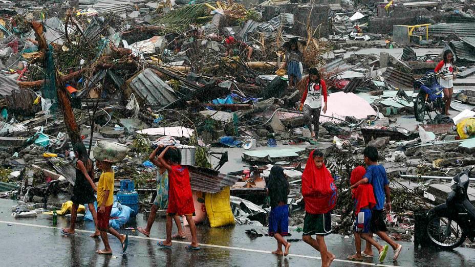 Sobreviventes carregam seus pertences entre casas destruídas pela passagem do supertufão Haiyan na cidade de Tacloban, na região central das Filipinas