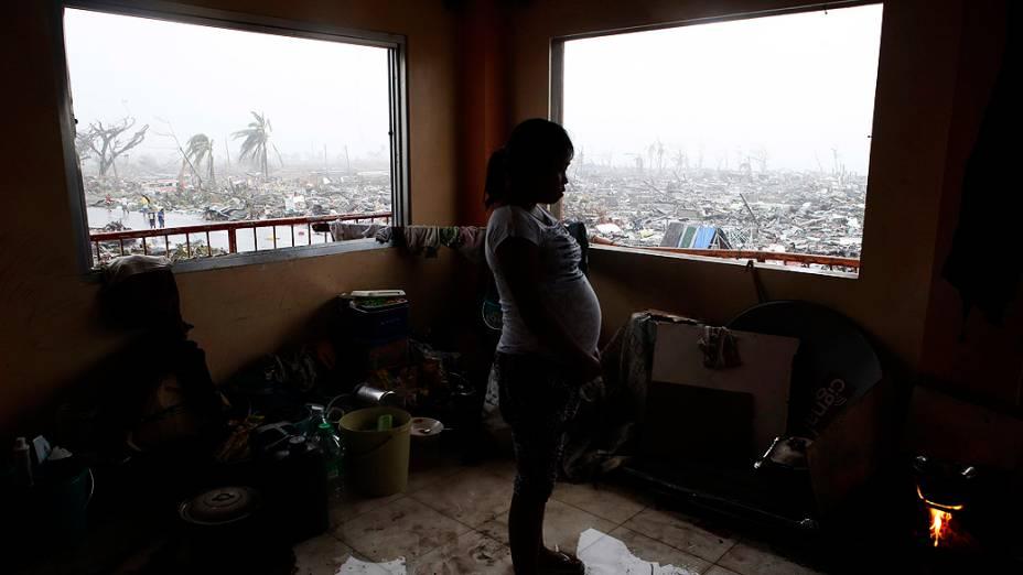 Grávida prepara refeição em um prédio que manteve-se de pé após passagem do supertufão Haiyan na cidade de Tacloban, região central das Filipinas