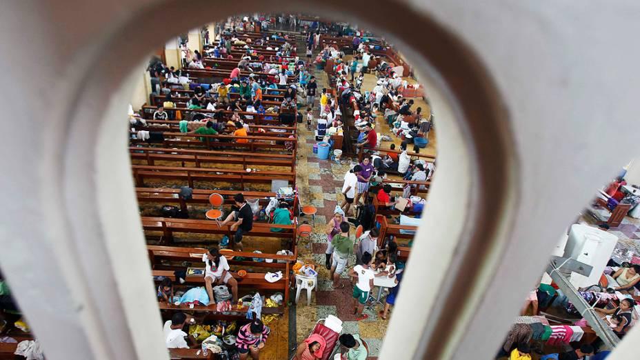 Sobreviventes procuram refúgio dentro de uma igreja católica que foi convertida em um centro de evacuação após a passagem do supertufão Haiyan na cidade Tacloban, Filipinas
