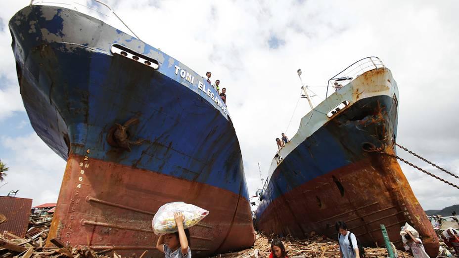 Sobreviventes passam por dois grandes barcos que foram arrastados por fortes ondas causadas pelo supertufão Haiyan na cidade de Tacloban, nas Filipinas