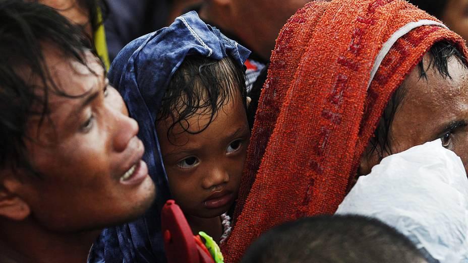 Homem tenta embarcar com seu filho em avião militar no aeroporto de Tacloban, a cidade foi devastada pela passagem do supertufão Haiyan, nas Filipinas