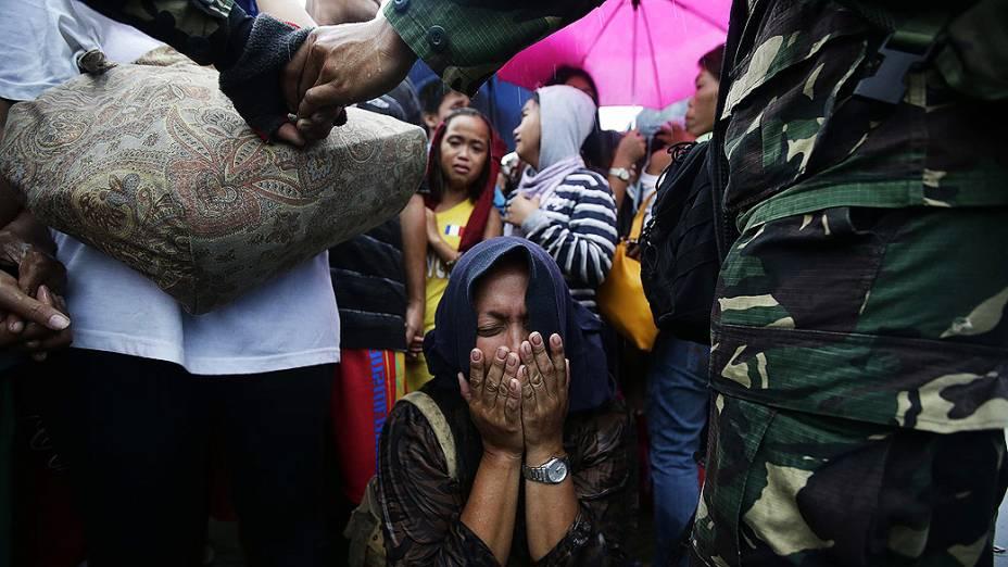 Mulher chora ao tentar embarcar em um avião de resgate no aeroporto da cidade de Tacloban